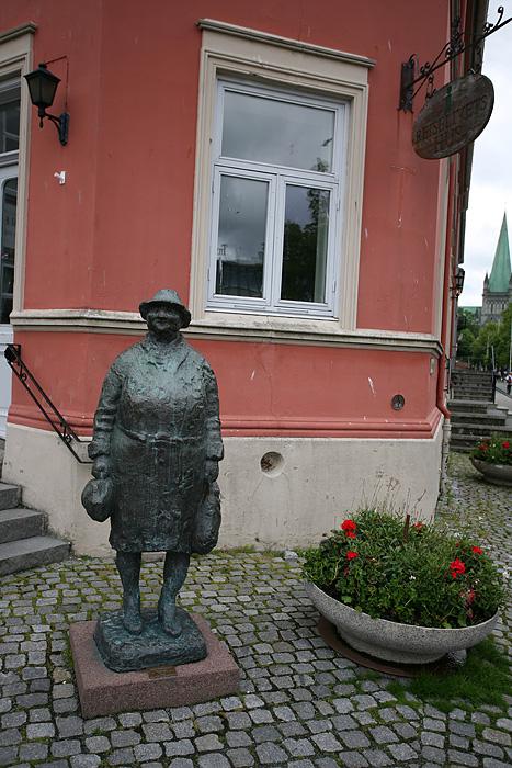 Il s'agit de la statue « Go Dagen » qui prend pour modèle une dame qui venait à Trondheim pour travailler comme femme de maison. Lorsqu'elle prit sa retraite, elle passa beaucoup de temps autour de la place Torget (là où est placée la statue), et tous ceux qui la saluaient recevaient en retour un joyeux « Go'dagen » (bien le bonjour). Mais point d'office du tourisme ici.