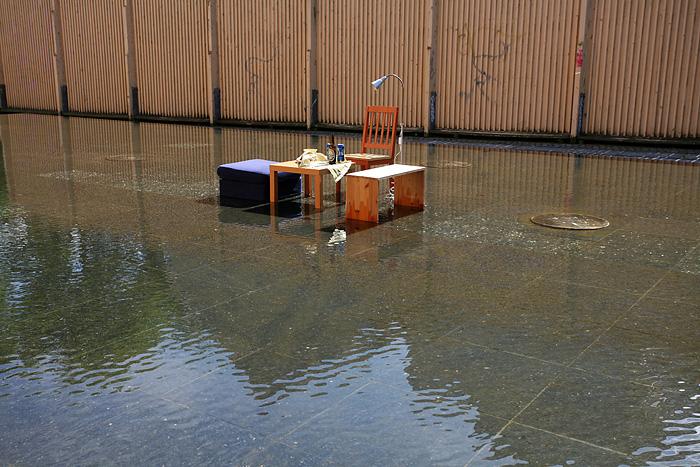 Une « œuvre d'art » : une table basse de salon avec l'apéro servi, en plein dans une fontaine
