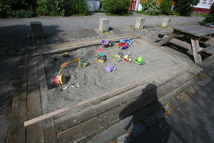 dans une rue semi-piétonne, un bac à sable « équipé » pour les petits