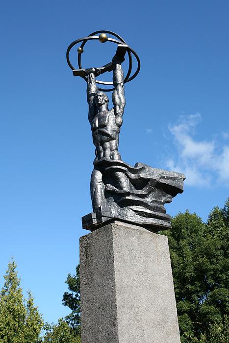 La statue d'un ouvrier musclé qui tient un atome. Normal.