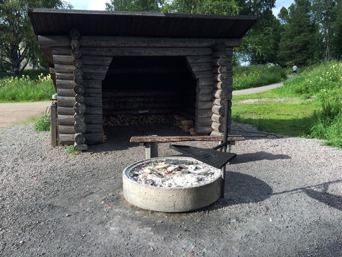 Deuxième fois qu'on voit ce genre d'aménagement en Finande. C'est une petite cabane avec du bois à disposition, un foyer et une grille. Il n'y a plus qu'à venir avec une alumette et de la viande et c'est la fiesta ! 5292 un banc face à la rivière
