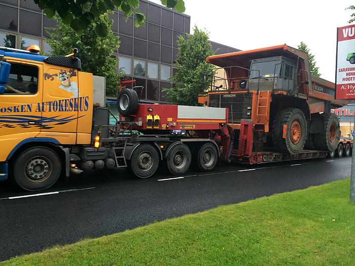 Un convoi exceptionnel transportant un tout petit camion passait par là pendant qu'on cherchait une place