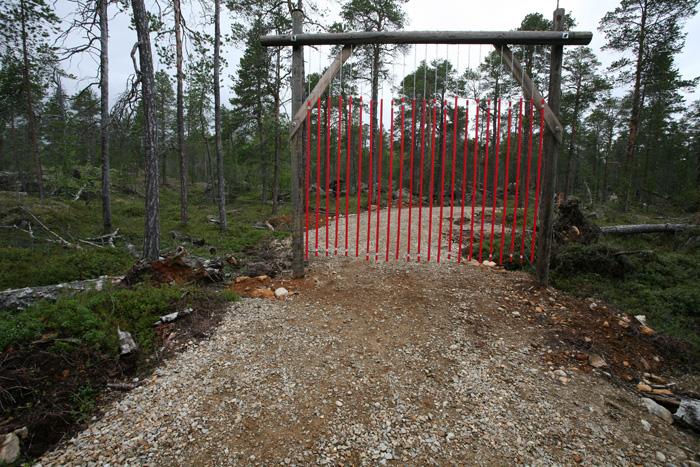sûrement une barrière anti-rennes. Ce sont des tubes de plastique rouge que l'on peut traverser comme un rideau, mais probablement que les rennes n'aiment pas ça.